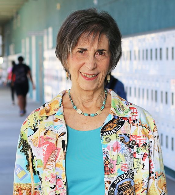 Joanne Sudman, Mentor at Take Stock in Children Hillsborough Education Foundation, older woman standing in school hallway smiling