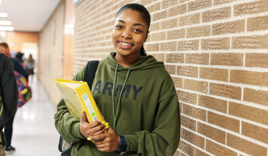 Young woman student wearing forest green ARMY hoodie, holding yellow binder, standing in front of brown brick wall, Hillsborough Education Foundation