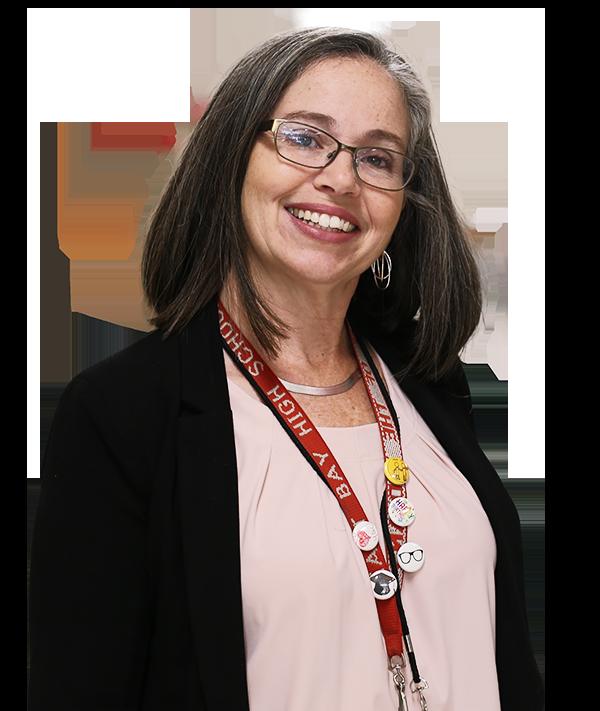 Corte de mujer de mediana edad con cabello negro, sonriente, con cordón con identificación y gafas, fondo transparente, Fundación Educativa de Hillsborough